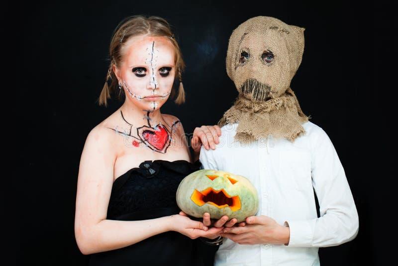 Muchacho y muchacha con el maquillaje de Halloween que sostiene la calabaza imagenes de archivo