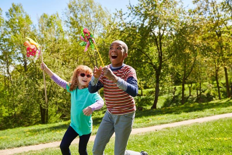Muchacho y muchacha con los molinoes de viento coloridos fotos de archivo libres de regalías