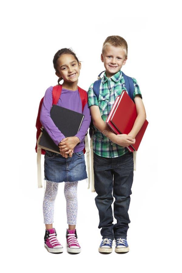Muchacho y muchacha de escuela con los packpacks que sostienen los libros fotos de archivo libres de regalías