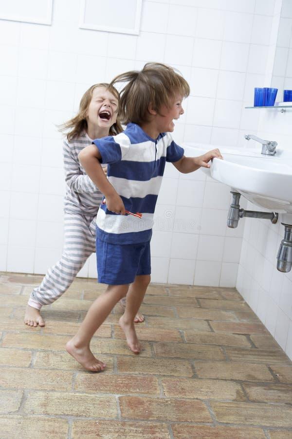 Muchacho y muchacha en dientes de cepillado del cuarto de baño foto de archivo