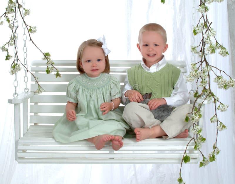 Muchacho y muchacha en el oscilación con el conejito foto de archivo libre de regalías