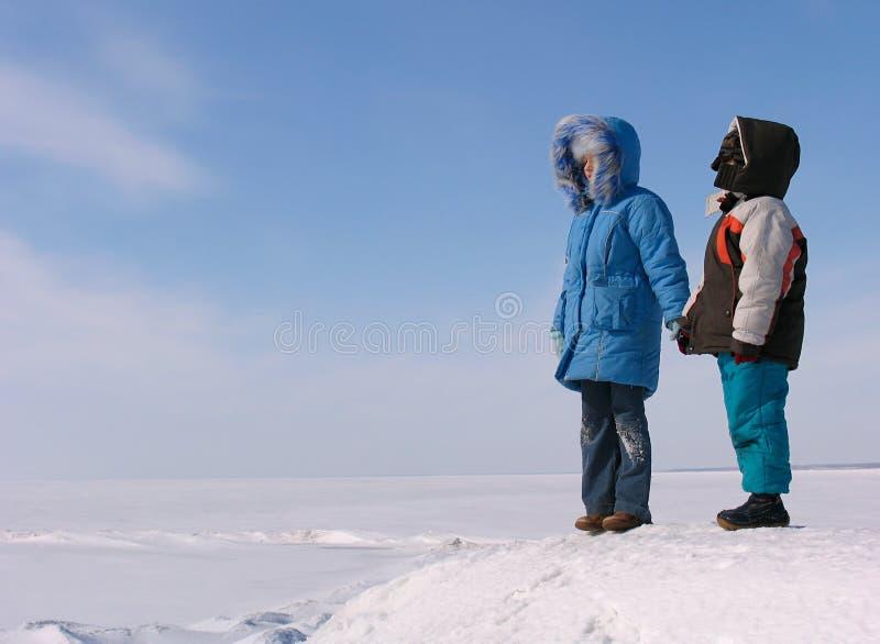 Muchacho y muchacha en la nieve imagenes de archivo