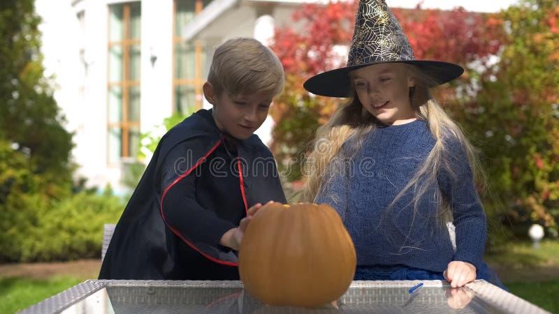 Muchacho y muchacha en los trajes de mascarada que dibujan la cara asustadiza en la calabaza, Halloween imagenes de archivo
