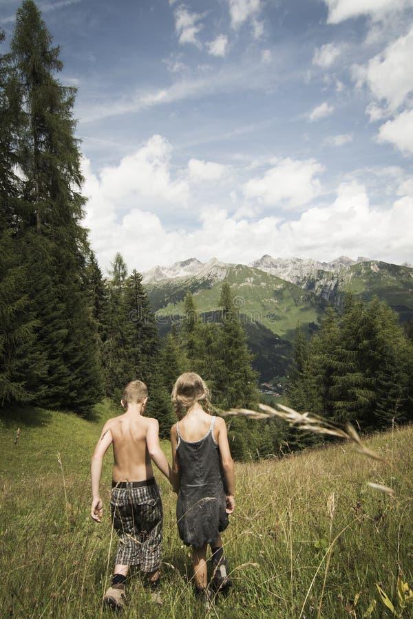 Muchacho y muchacha en montañas foto de archivo