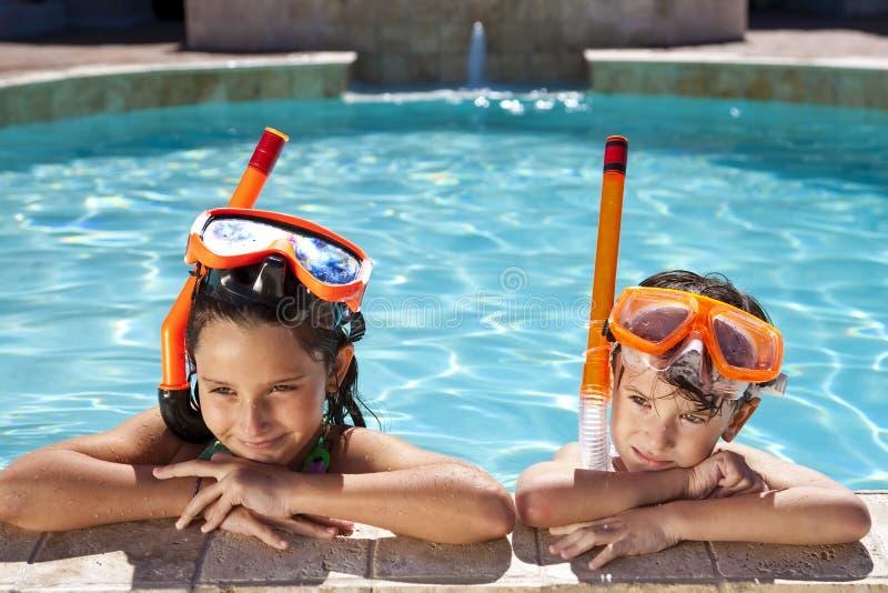 Muchacho y muchacha en piscina con los anteojos y el tubo respirador fotografía de archivo libre de regalías