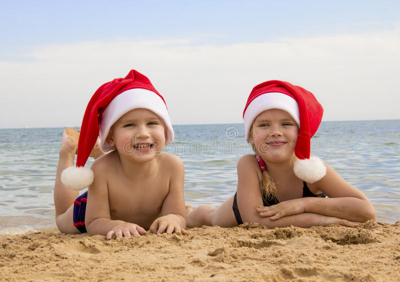 Muchacho y muchacha en un sombrero de santa en la sonrisa de la playa foto de archivo libre de regalías