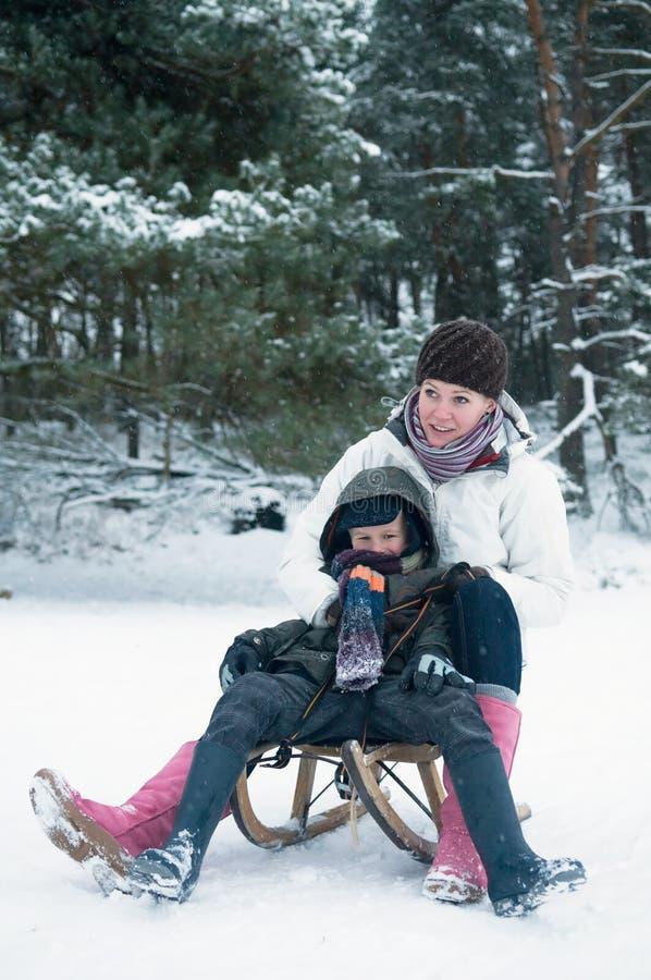 Muchacho y muchacha en un trineo foto de archivo