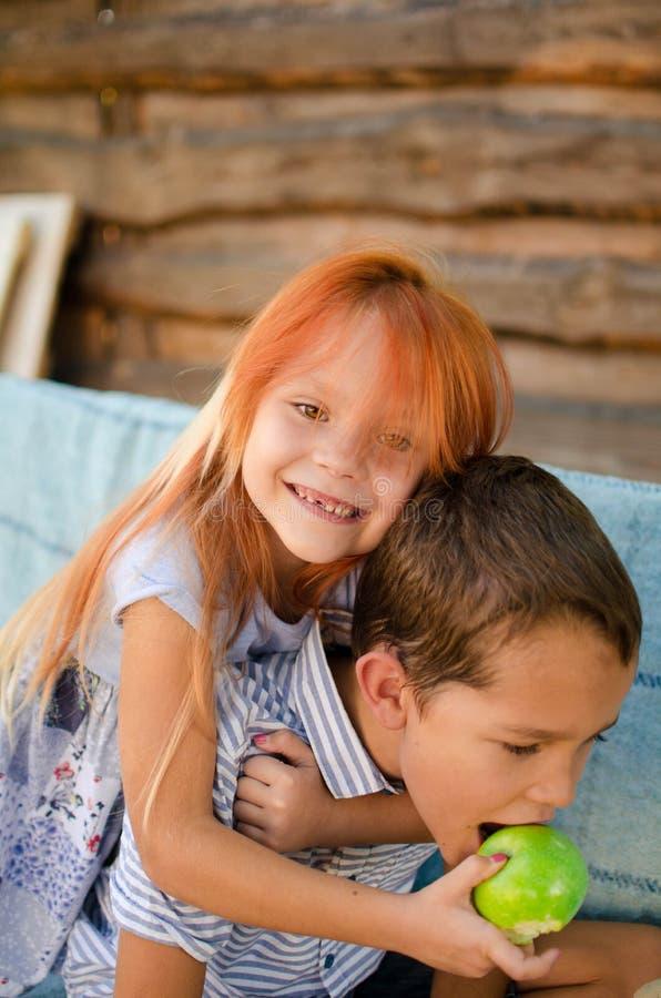 Muchacho y muchacha felices en un oscilación en el jardín La hermana alimenta sus manzanas del verde del hermano Niños de risa, n fotografía de archivo