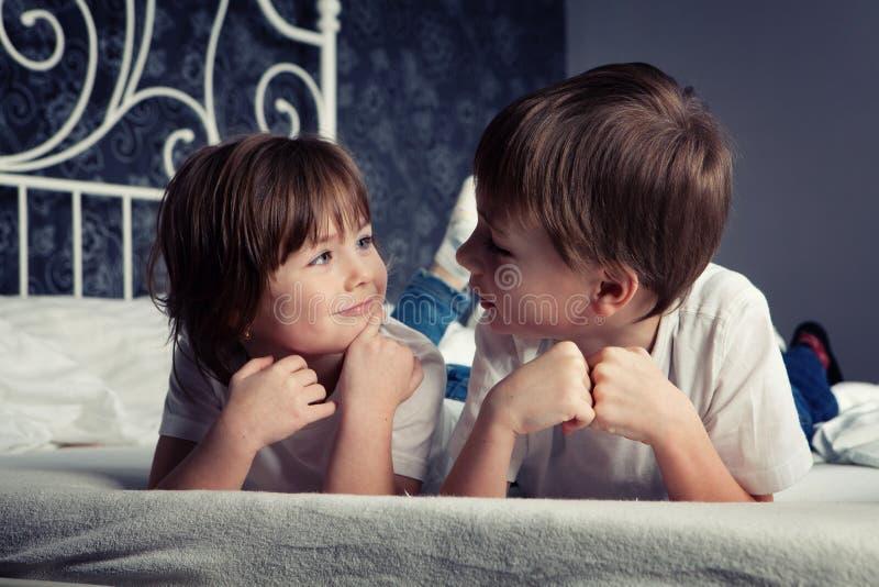 Muchacho y muchacha jovenes en cama fotografía de archivo libre de regalías