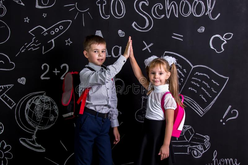 Muchacho y muchacha La escuela acopla la situación antes de la pizarra como fondo con una mochila en su claping de las partes pos fotos de archivo