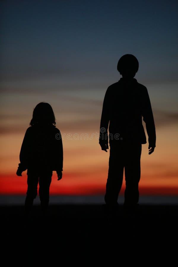 Muchacho y muchacha - puesta del sol en la playa foto de archivo libre de regalías