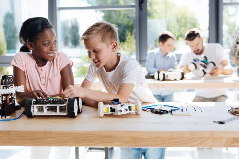 Muchacho y muchacha que discuten la construcción de un coche robótico imagen de archivo