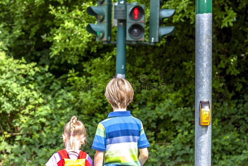 Muchacho y muchacha que esperan en el semáforo rojo fotografía de archivo