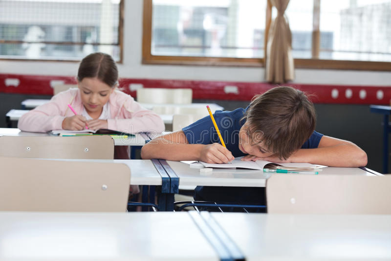 Muchacho y muchacha que estudian en sala de clase fotografía de archivo libre de regalías