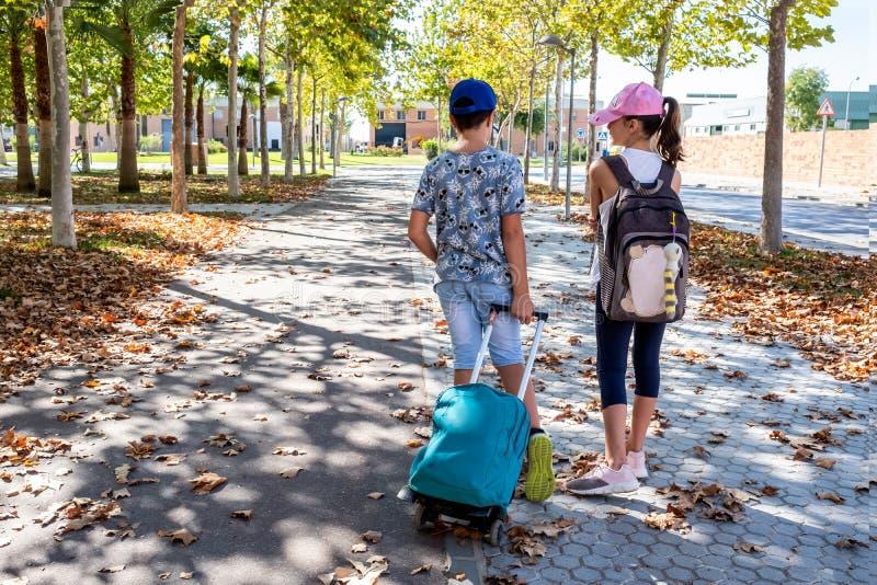 Muchacho y muchacha que hablan van a la escuela con sus mochilas foto de archivo libre de regalías