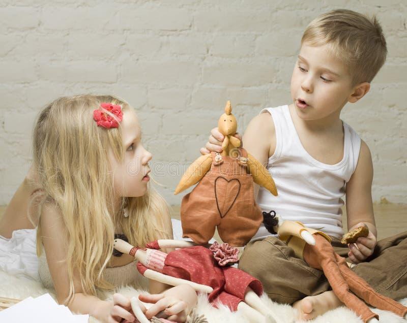 Muchacho y muchacha que juegan con los animales rellenos fotografía de archivo libre de regalías