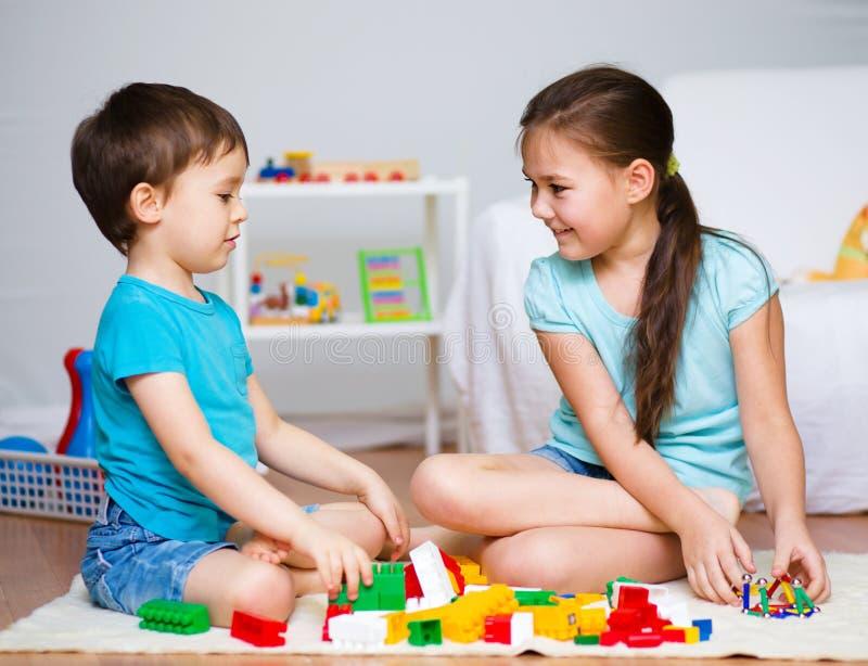 Muchacho y muchacha que juegan con los juguetes imágenes de archivo libres de regalías