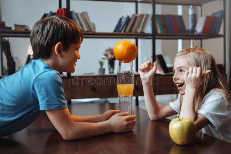 Muchacho y muchacha que juegan con los vidrios y las frutas en la cocina junto fotos de archivo