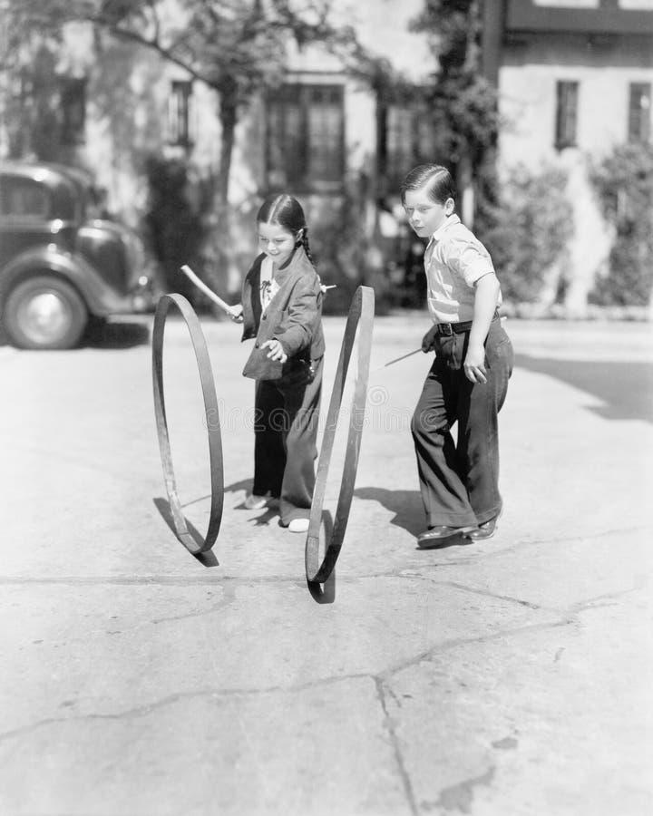 Muchacho y muchacha que juegan el aro y el palillo en una acera (todas las personas representadas no son vivas más largo y ningún fotos de archivo libres de regalías