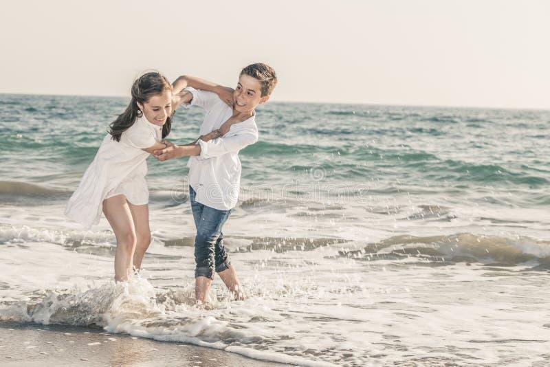 Muchacho y muchacha que juegan en la costa fotos de archivo libres de regalías