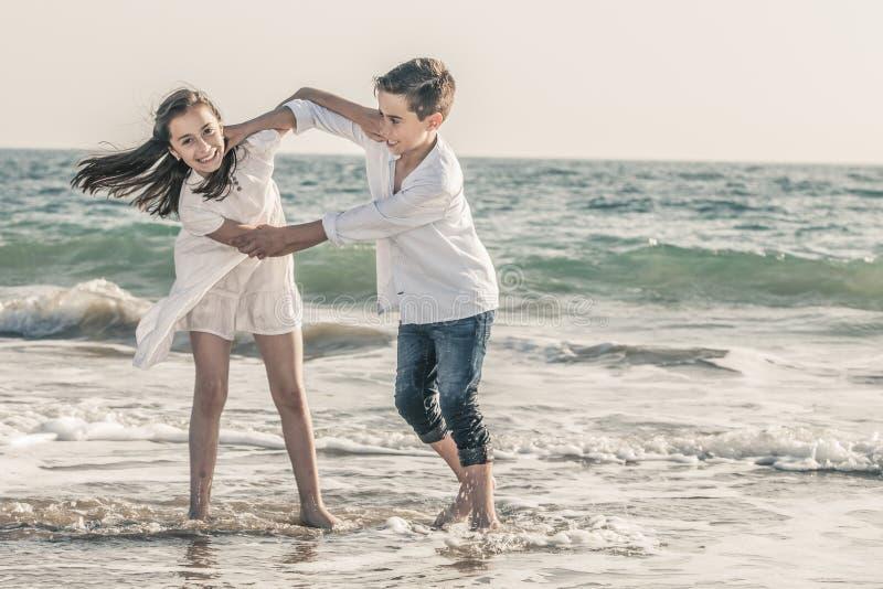 Muchacho y muchacha que juegan en la costa imagen de archivo
