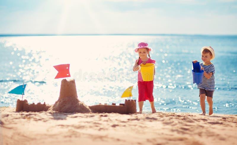 Muchacho y muchacha que juegan en la playa imagen de archivo