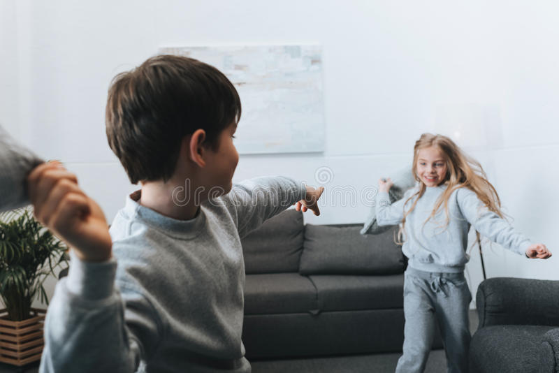 Muchacho y muchacha que juegan lucha de almohada en casa imagenes de archivo