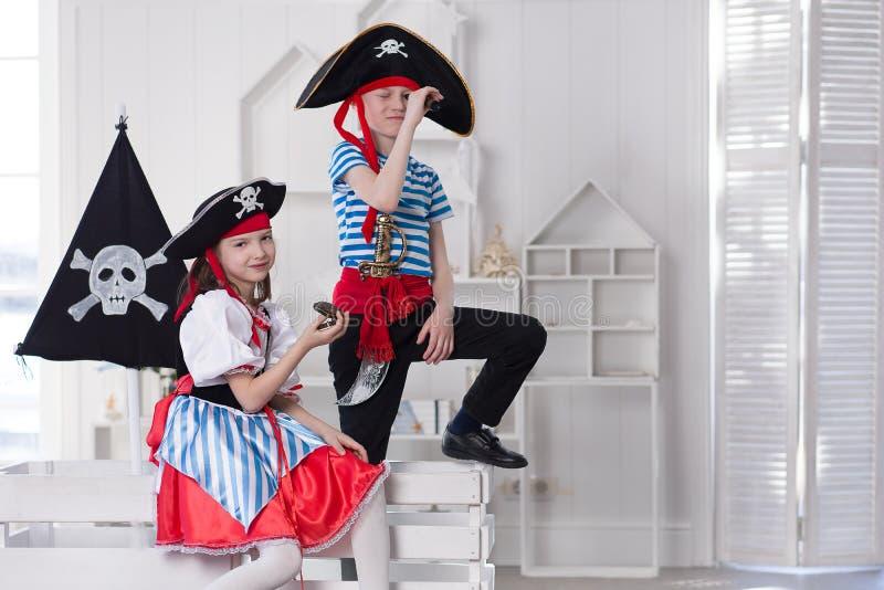 Muchacho y muchacha que juegan a piratas Est?n llevando los trajes del pirata foto de archivo libre de regalías
