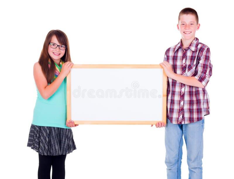 Muchacho y muchacha que llevan a cabo a un tablero de publicidad vacío imagenes de archivo