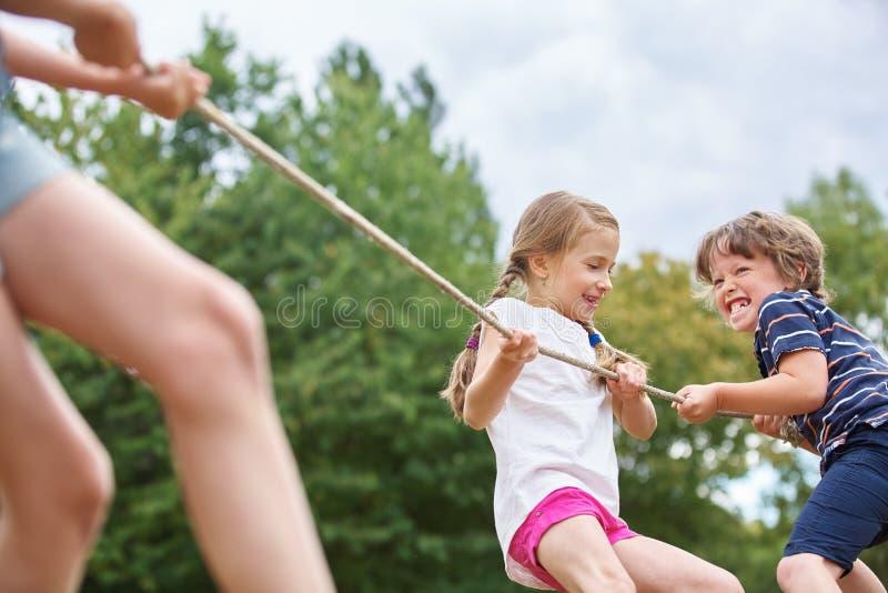 Muchacho y muchacha que tiran de una cuerda imagen de archivo libre de regalías