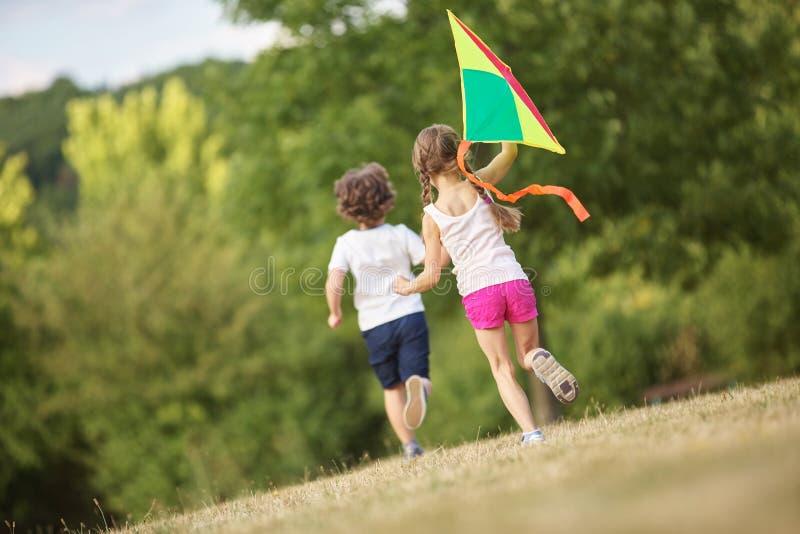 Muchacho y muchacha que vuelan una cometa imagen de archivo