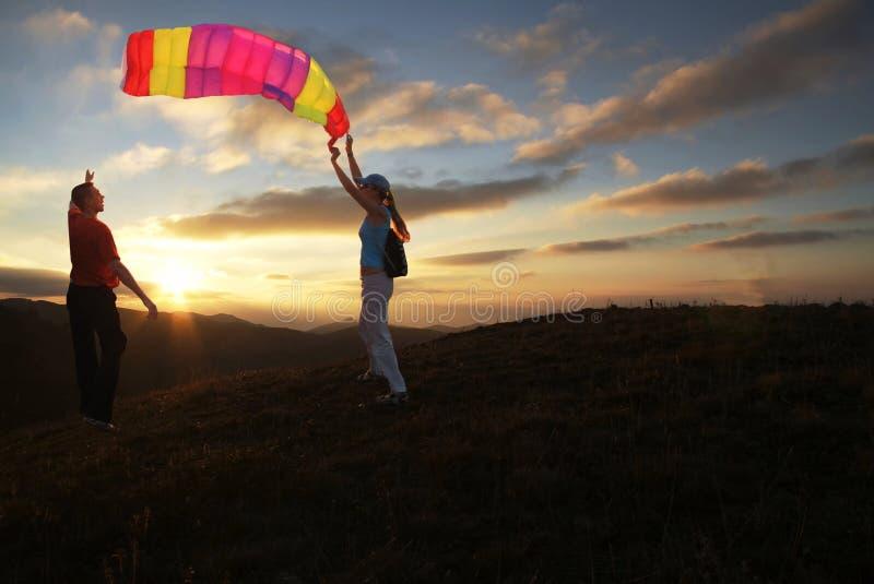 Muchacho y muchacha que vuelan una cometa en puesta del sol imagenes de archivo