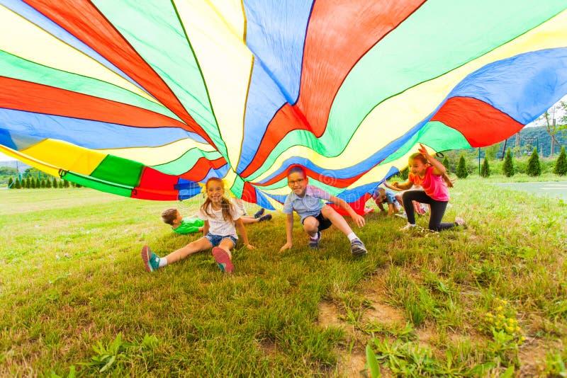 Muchacho y muchacha sonrientes debajo del paracaídas colorido imagen de archivo libre de regalías
