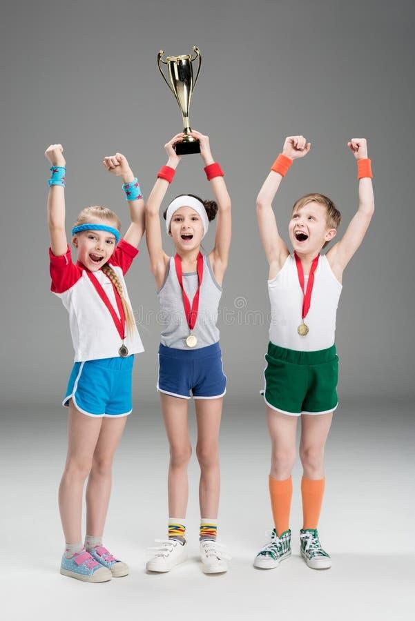 Muchacho y muchachas emocionados con las medallas y el cubilete del campeón imagenes de archivo