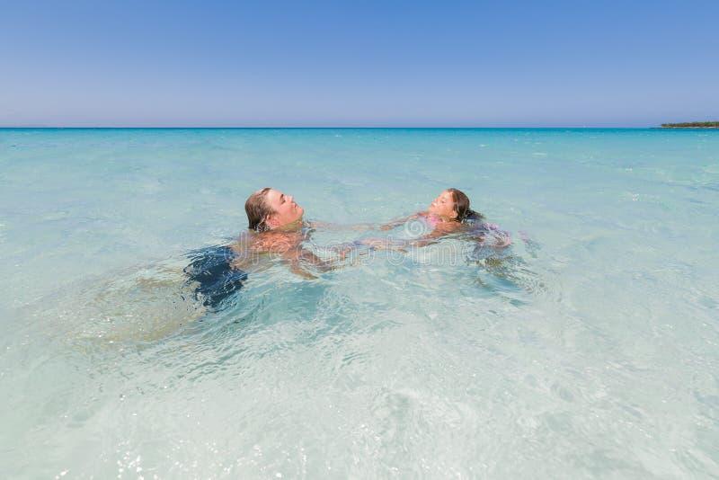 Muchacho y niña que relajan, nadando y disfrutando allí del tiempo libre en el océano fotografía de archivo
