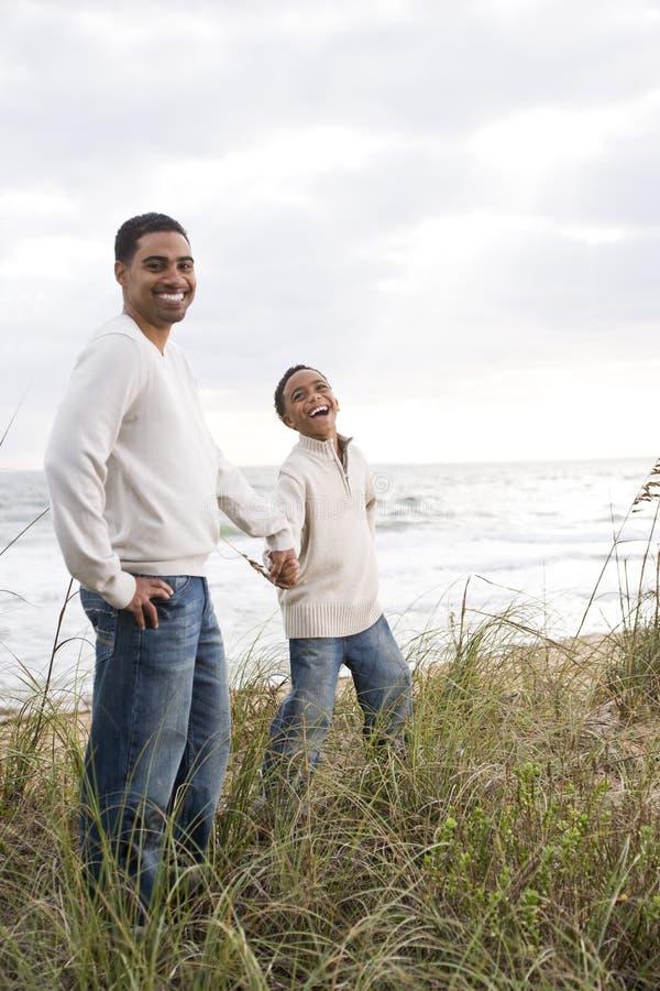 Muchacho y padre del African-American en la duna de arena de la playa imagenes de archivo
