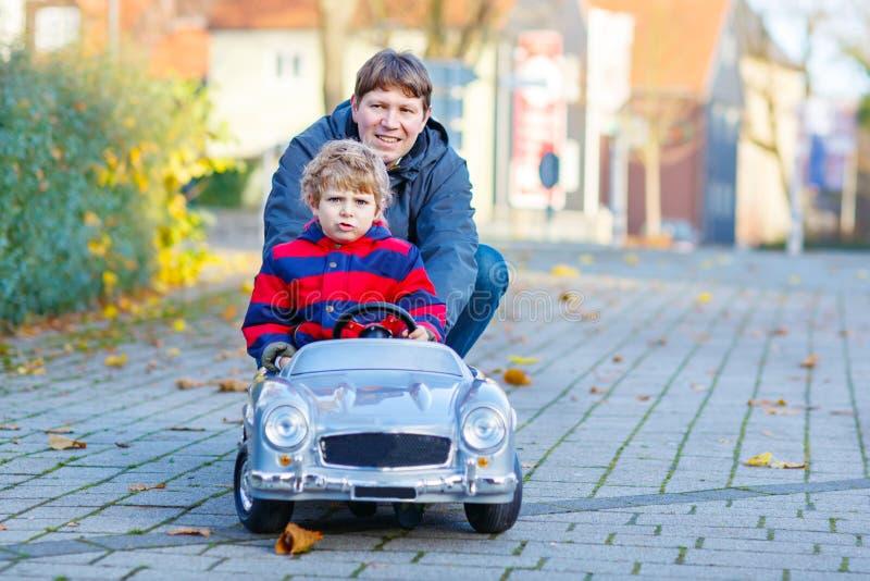 Muchacho y padre del niño que juegan con el coche, al aire libre fotos de archivo libres de regalías