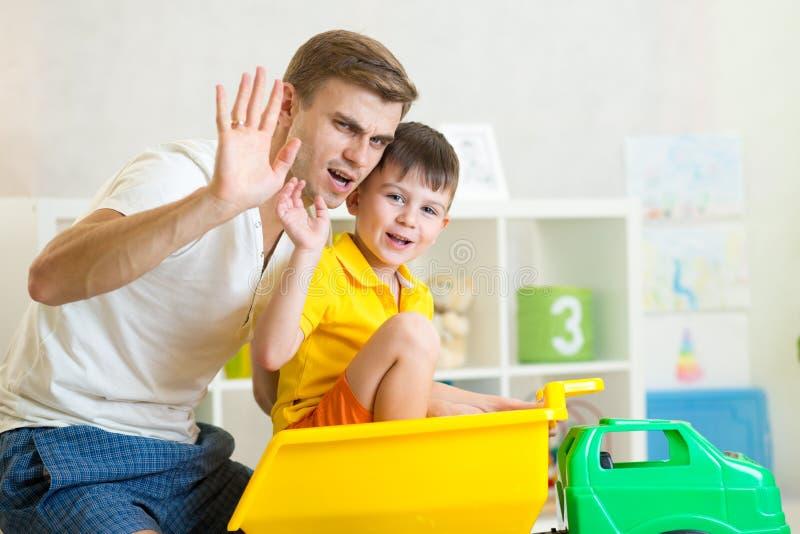 Muchacho y padre del niño que juegan con el tronco del juguete imagen de archivo