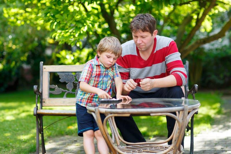 Muchacho y padre del niño que juegan junto al juego de los inspectores fotografía de archivo