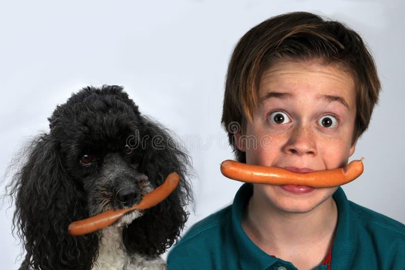 Muchacho y perro que comen las salchichas imagenes de archivo