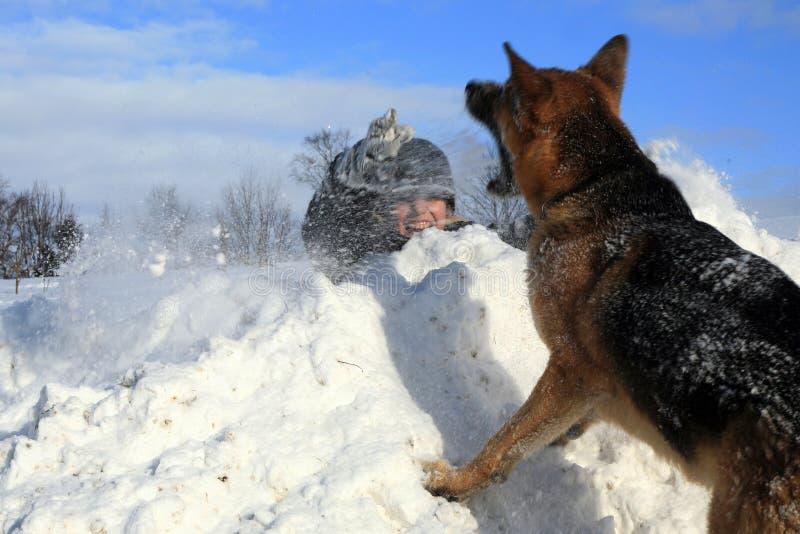 Muchacho y perro que juegan en nieve imagen de archivo