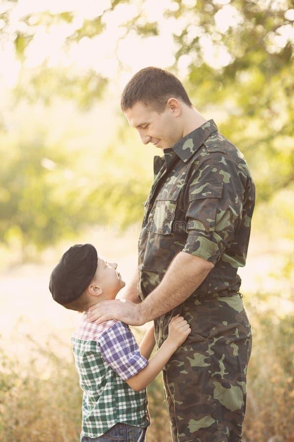 Muchacho y soldado en un uniforme militar imagen de archivo