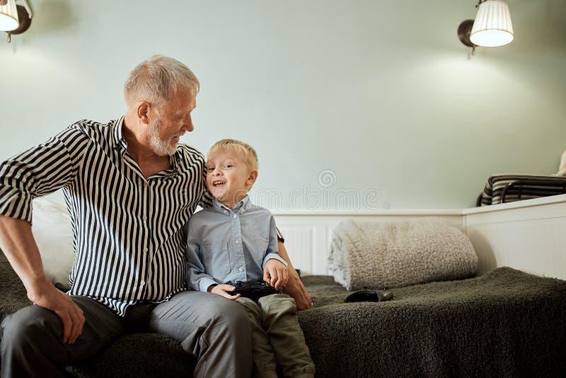 Muchacho y su abuelo que pasan el tiempo junto que se relaja en el sofá acogedor en casa imagenes de archivo