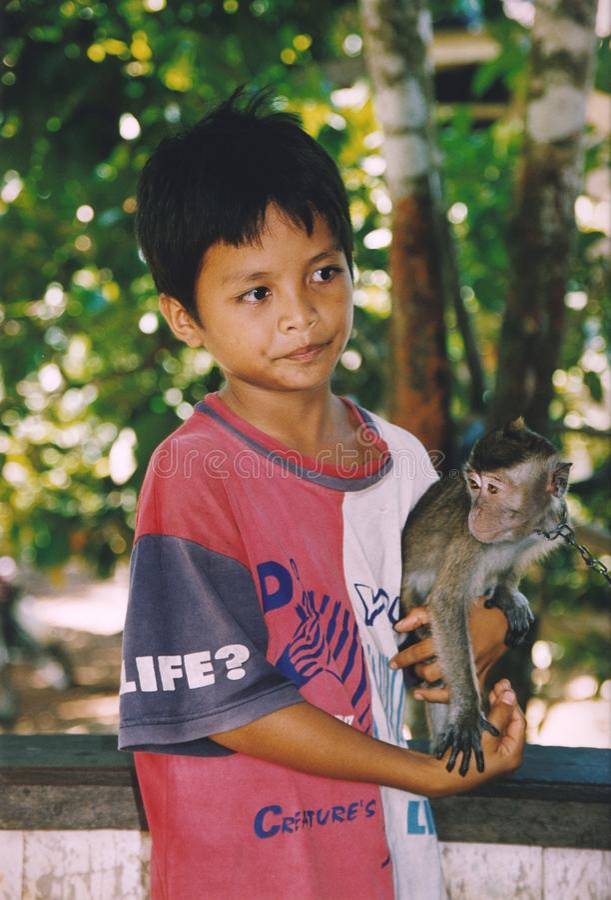 Muchacho y su amigo del mono en Kalimantan, Indonesia imagen de archivo libre de regalías