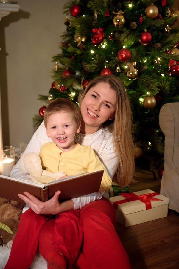 Muchacho y su mamá que leen un libro junto que ríe fotografía de archivo libre de regalías