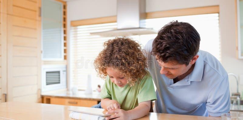 Muchacho y su padre que usa un ordenador de la tablilla foto de archivo