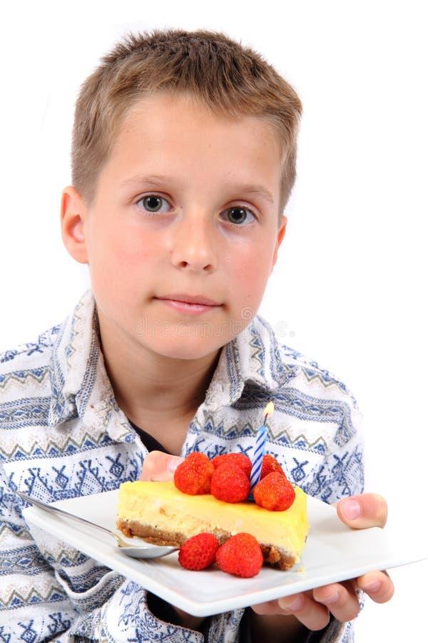 Muchacho y su pastel de queso del cumpleaños fotografía de archivo libre de regalías