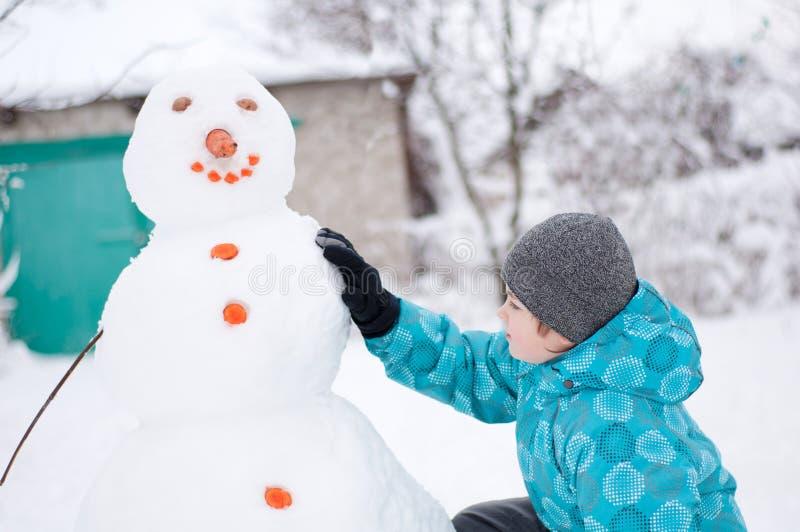 Muchacho y un muñeco de nieve - día de fiesta de invierno imagen de archivo