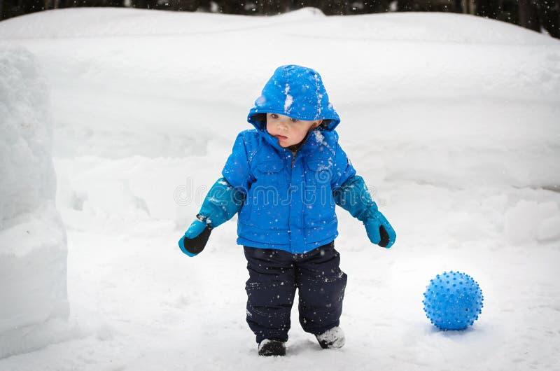 Muchacho y una bola afuera en la nieve fotografía de archivo libre de regalías