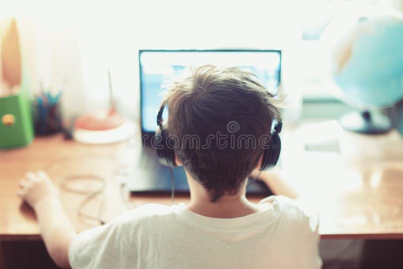 Muchacho zurdo del videojugador talentoso que juega en el ordenador portátil imagenes de archivo